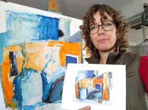 artist phoebe thomasson holding a print of her painting